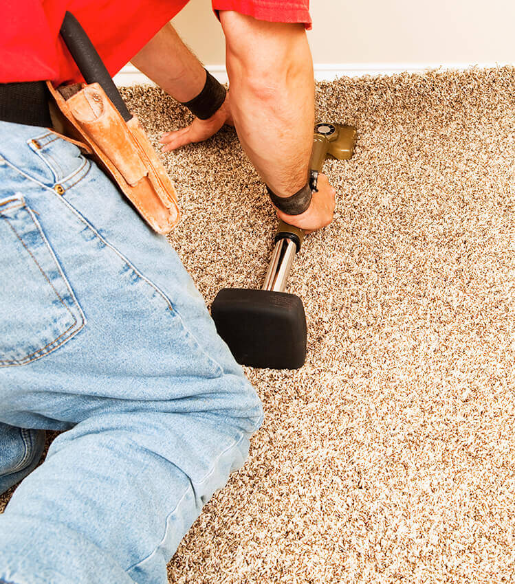 Photograph of a workman fitting a new brown carpet