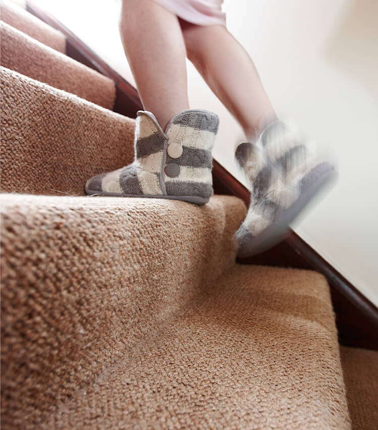 Photograph of a person wearing slippers walking up a newly laid carpet on stairs